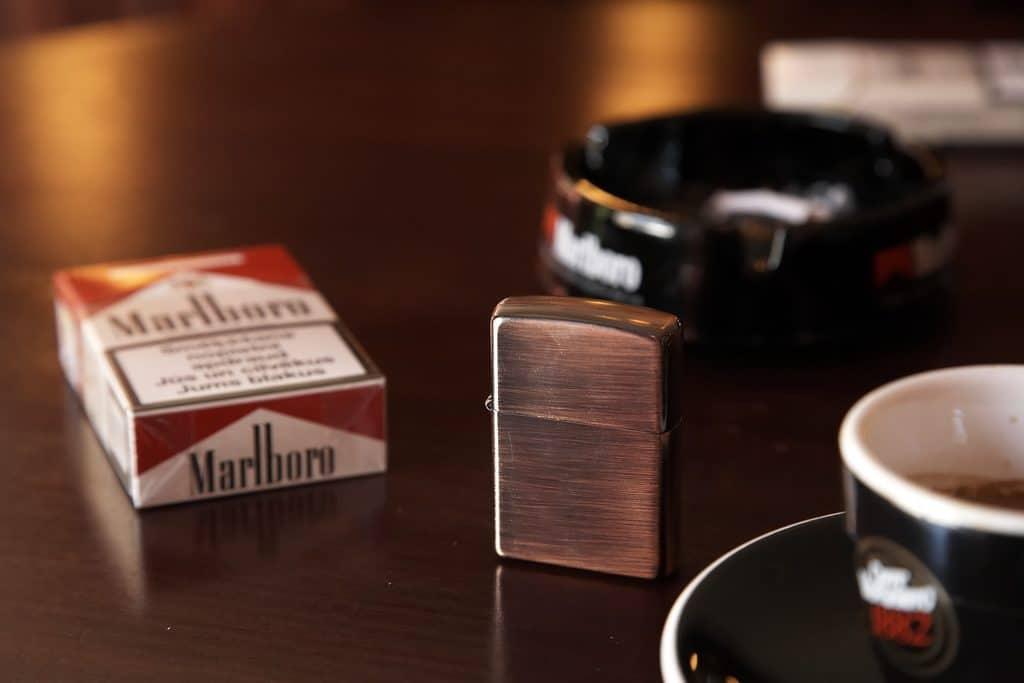 paquet de cigrette avec un briquet, un cendrier et une tasse de café